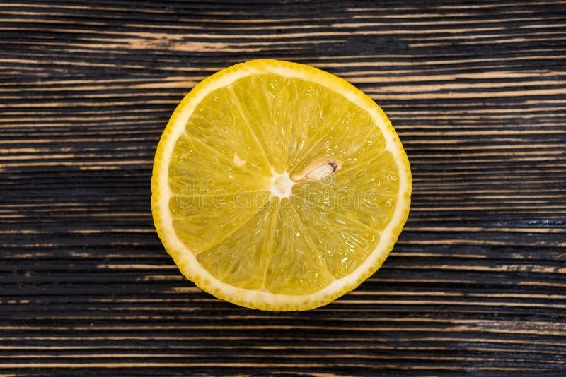 Лимон отрезанный неполной вырубкой свежий на деревянной предпосылке таблицы, деревенском стиле стоковое фото