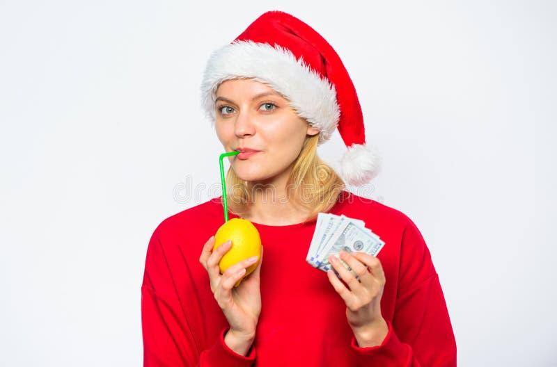 Лимон сока питья шляпы santa девушки пока деньги кучи владением Заработайте деньги на свежем лимонаде Концепция выгоды рождества  стоковая фотография rf