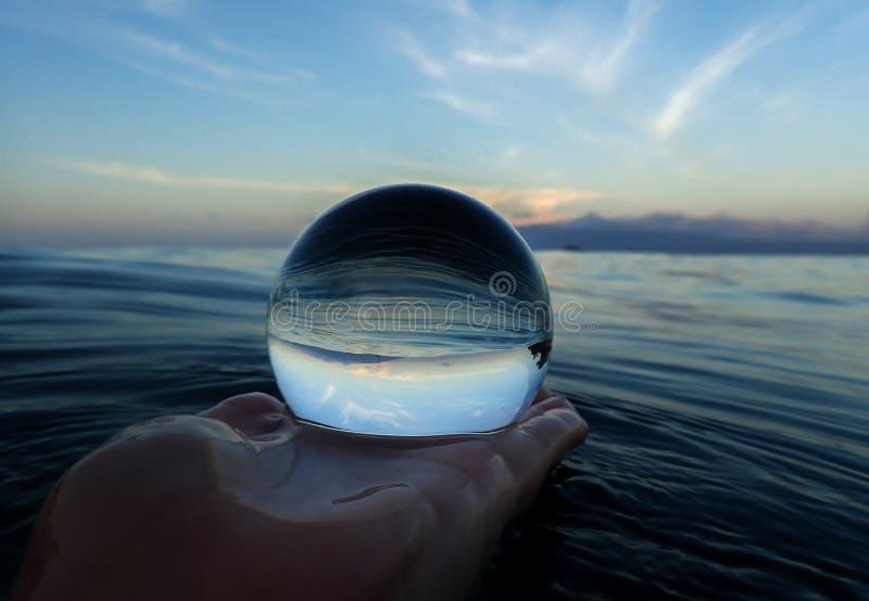 Линии и текстуры океана поверхностные с островом на горизонте захватили в шарике стоковое фото rf