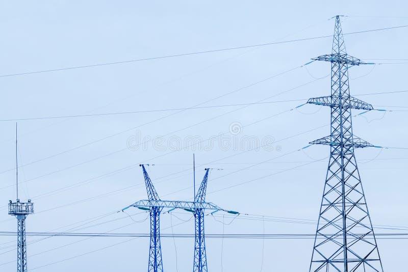 Линии электропередач на предпосылке конца-вверх голубого неба Силуэт электрического поляка с космосом экземпляра стоковое изображение