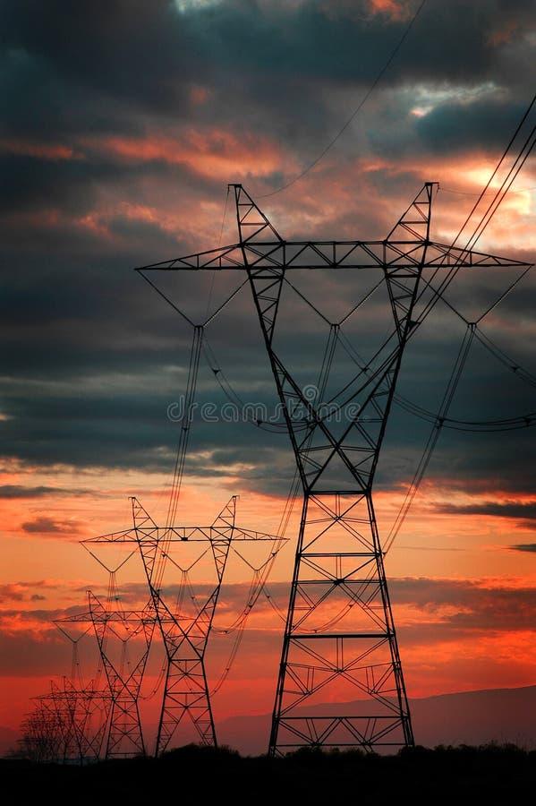 Линии электропередач для башен и захода солнца металла электричества стоковая фотография