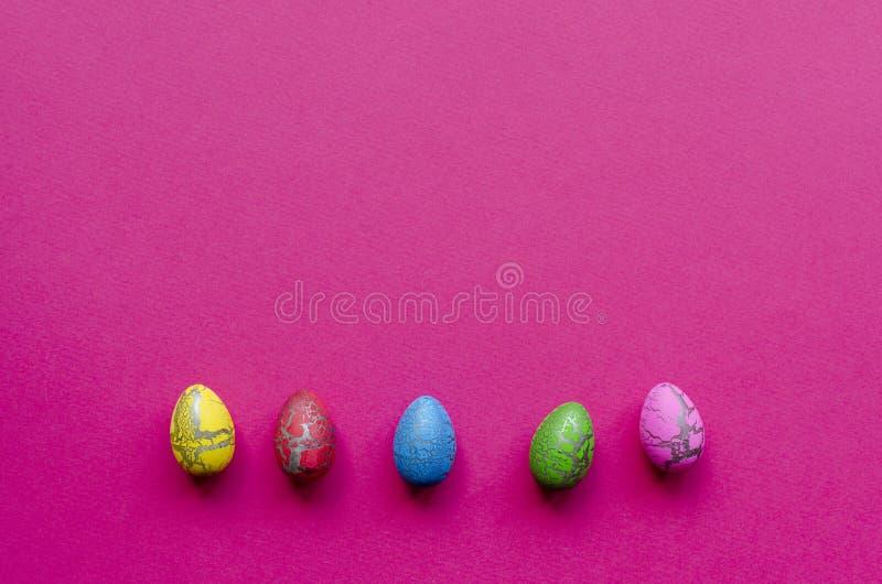 Линия покрашенных пасхальных яя на розовой бумажной предпосылке стоковые фото