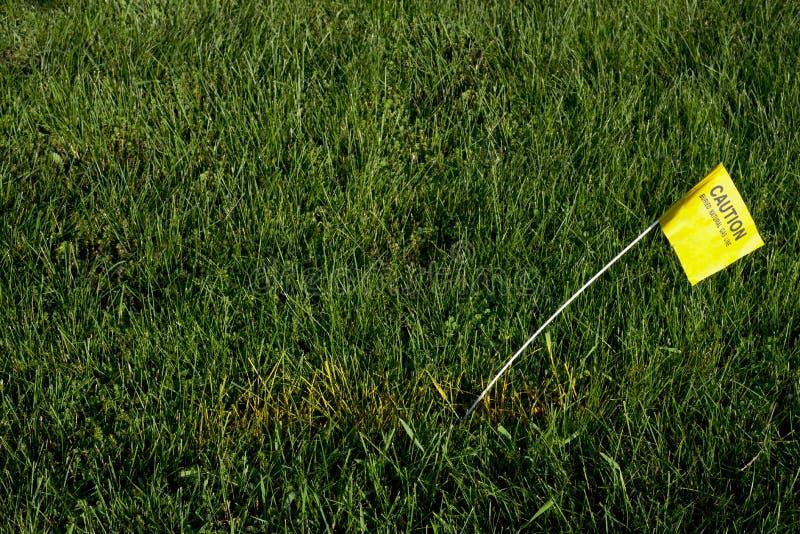 Линия природного газа горячей линии землекопа похороненная флагом стоковое изображение