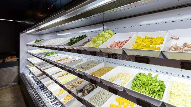 Линия свежих продуктов для шведского стола sukiyaki в холодильнике как цыпленок, свинина, говядина, шарик мяса, рыба, овощи, тофу стоковая фотография
