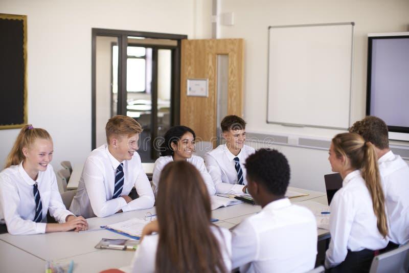 Линия студентов средней школы нося равномерное усаживание на столе в классе стоковые изображения