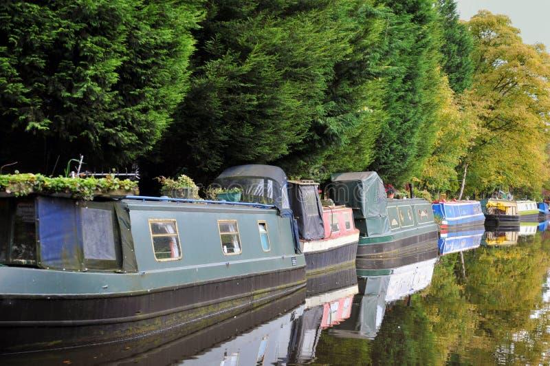 Линия традиционных узких шлюпок и плавучих домов причаленных вдоль канала с деревьями отразила в неподвижной воде в лете стоковая фотография