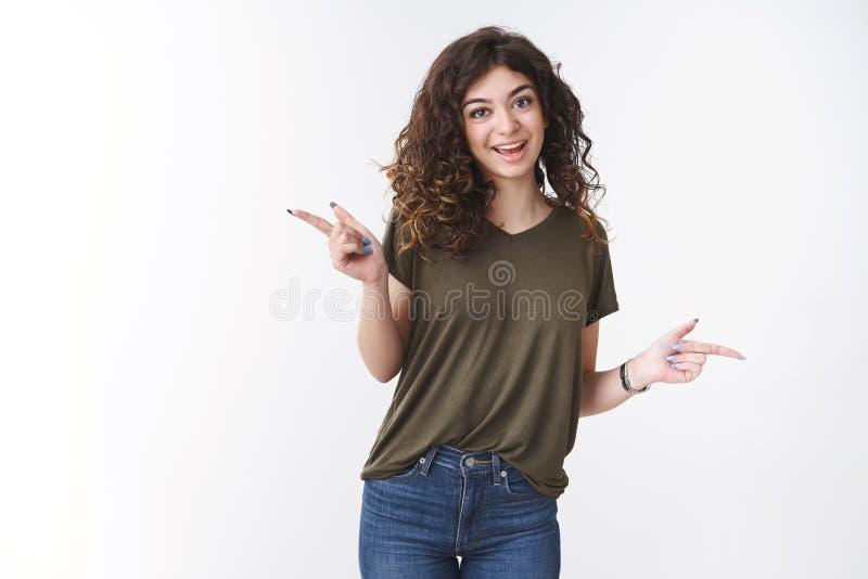 Липкая симпатичная выходящая девушка с кудрявыми волосами в оливковой футболке танцует радостно указывая налево направо стоковые изображения