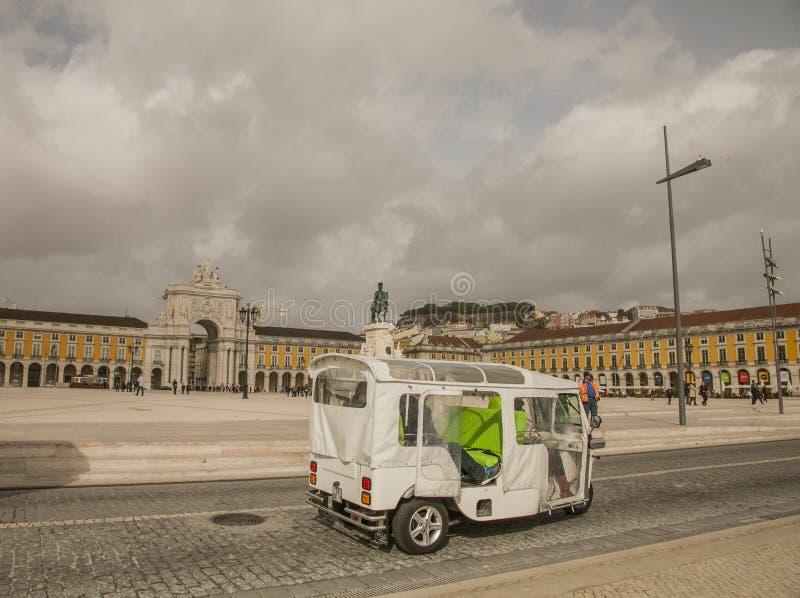 Лиссабон - облачные небеса над желтым квадратом; туристы двигая вокруг стоковая фотография