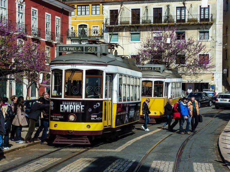 ЛИССАБОН, ПОРТУГАЛИЯ - 7-ОЕ АПРЕЛЯ 2013: Туристы входя в желтый трамвай, Лиссабон, Португалию стоковые фото