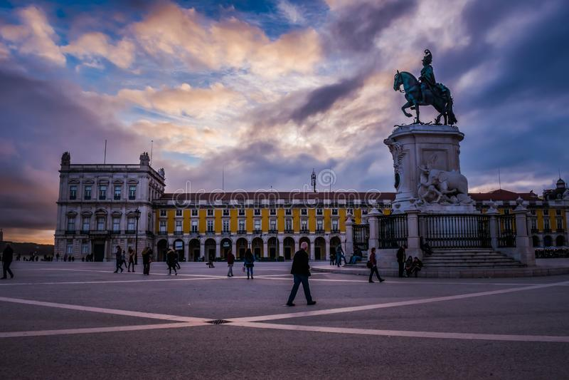 Лиссабон, Португалия - 17-ое марта 2019 - красочный заход солнца над Praça делает Comércio, людей идя рядом с конноспортивной с стоковое изображение