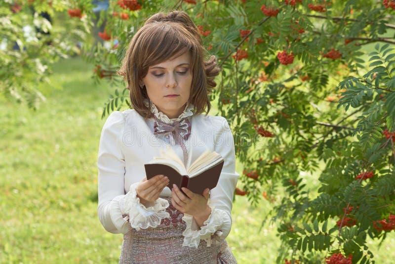 Листья девушки через книгу стоковое фото rf