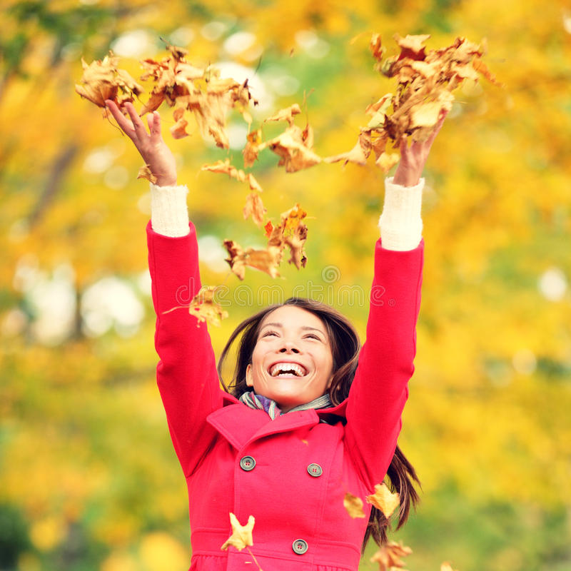 Листья женщины осени/падения счастливые бросая стоковое фото rf