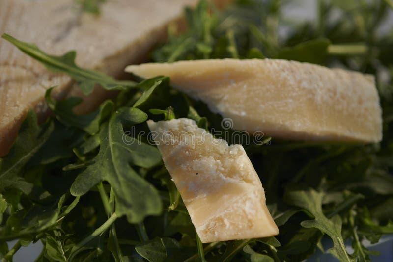 Листья Ракеты и итальянская крупная нарезка трудного сыра стоковая фотография