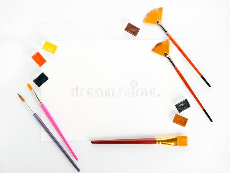 Лист бумаги с щетками и красками на белой предпосылке стоковое фото