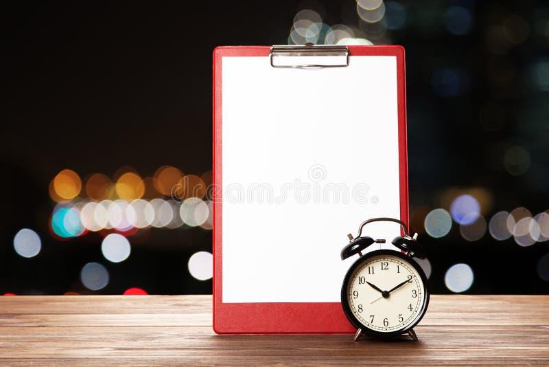 Лист и будильник чистого листа бумаги стоковое фото