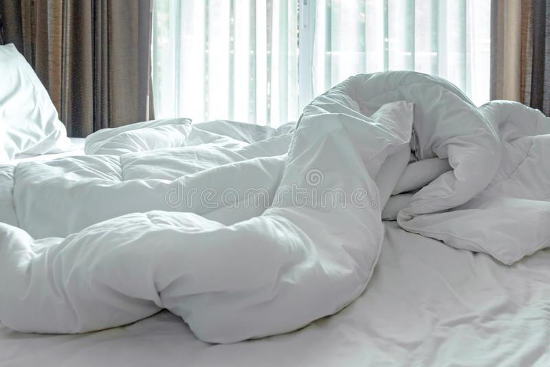 Лист, одеяло и подушка кровати тюфяка белые, messed вверх в утре в комнате кровати стоковая фотография