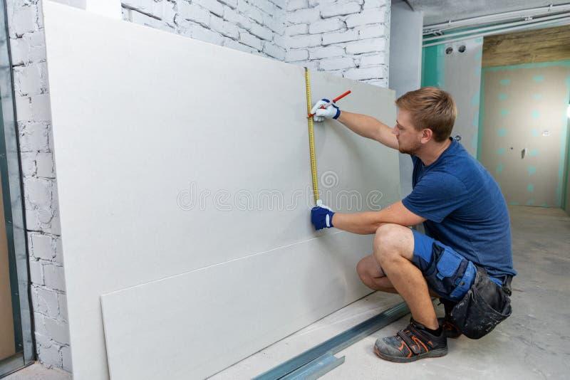 Лист штукатурной плиты человека измеряя для внутренней конструкции стоковое изображение