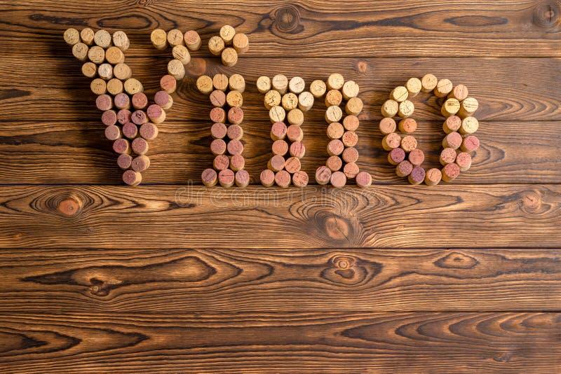Литерность Vino сделанная пробочек на деревянной предпосылке стоковая фотография rf