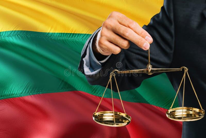 Литовский судья держит золотые весы правосудия с предпосылкой флага Литвы развевая Тема равности и законная концепция бесплатная иллюстрация