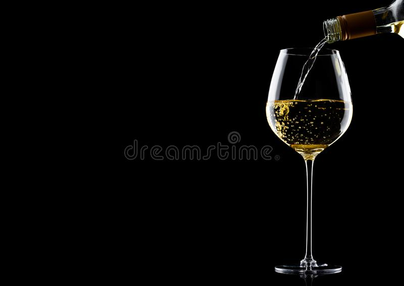 Лить белое вино от бутылки к стеклу на черноте с космосом для вашего текста стоковые фото