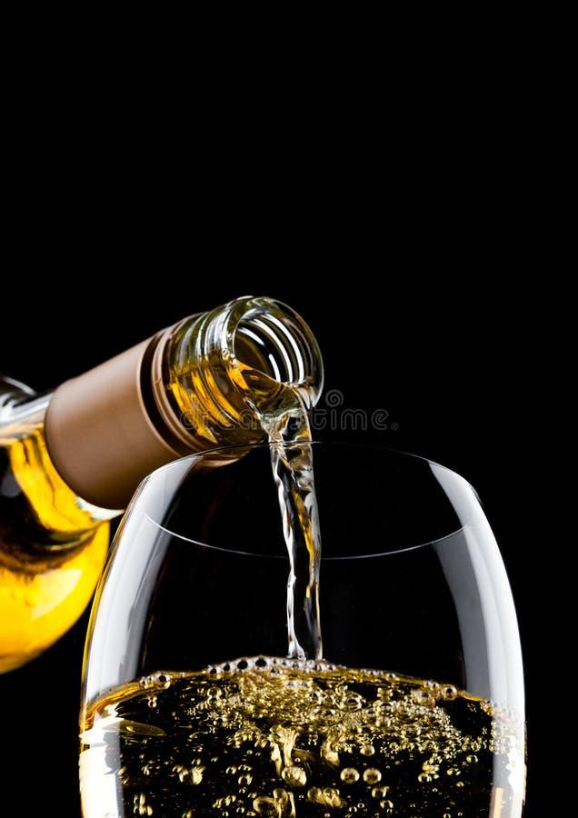 Лить белое вино от бутылки к стеклу на черноте стоковая фотография rf
