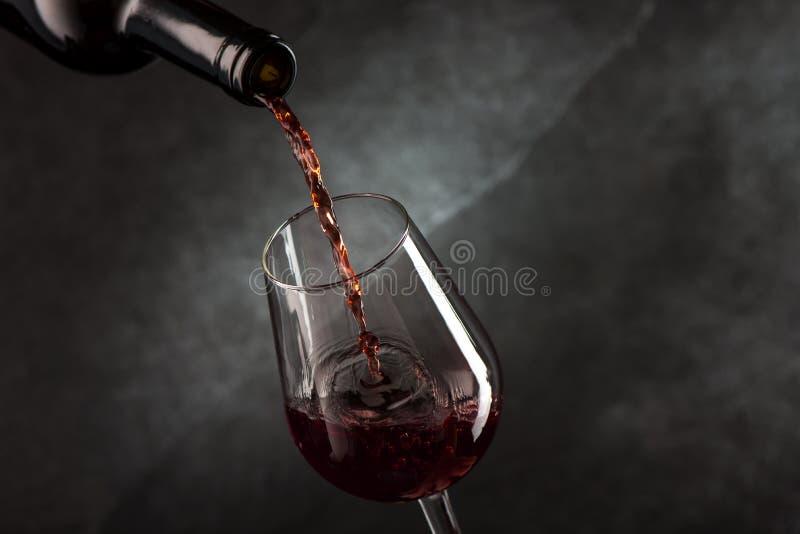 Лить вино от бутылки к стеклу стоковое фото rf