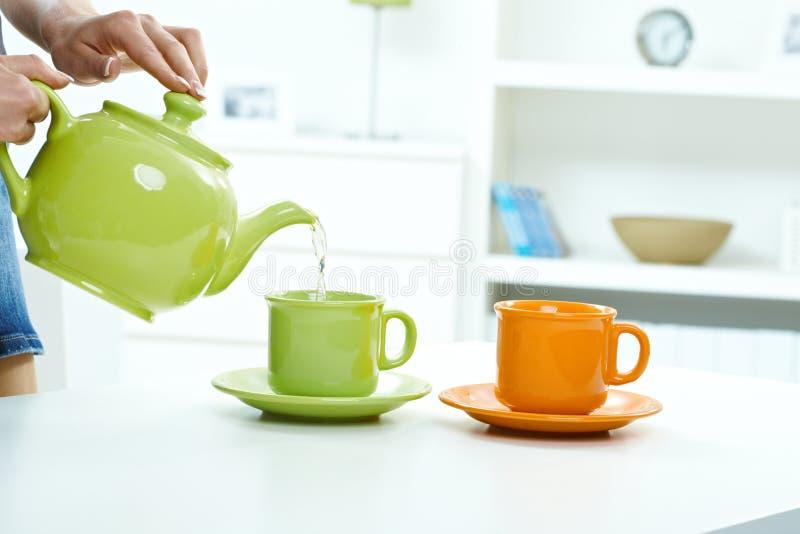 Лить вода от чайника к светлому тоновому изображению кружки стоковое изображение