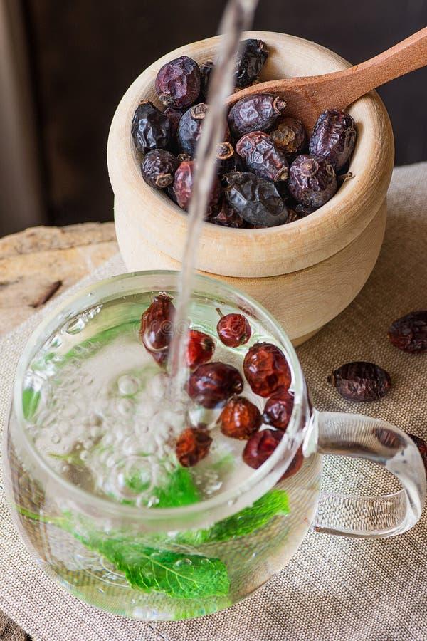 Лить горячая вода в стеклянную чашку заваривая чай розового бедра с ягодами свежей мяты в медицине деревянного полотенца шара Lin стоковая фотография rf