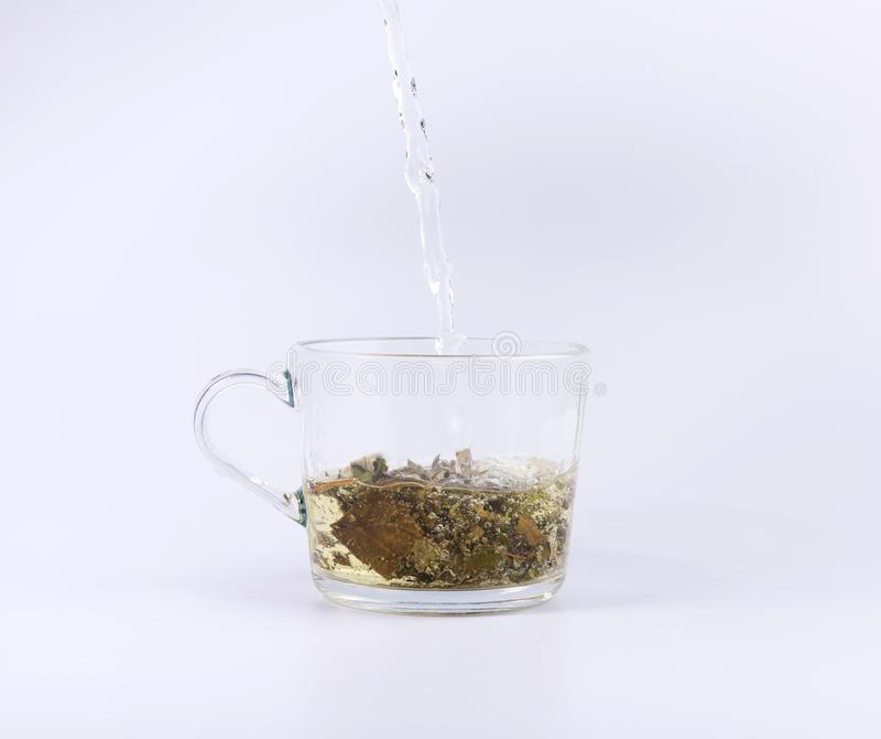 Лить горячая вода к стеклянной чашке с чаем, изолированным на белизне стоковое фото rf