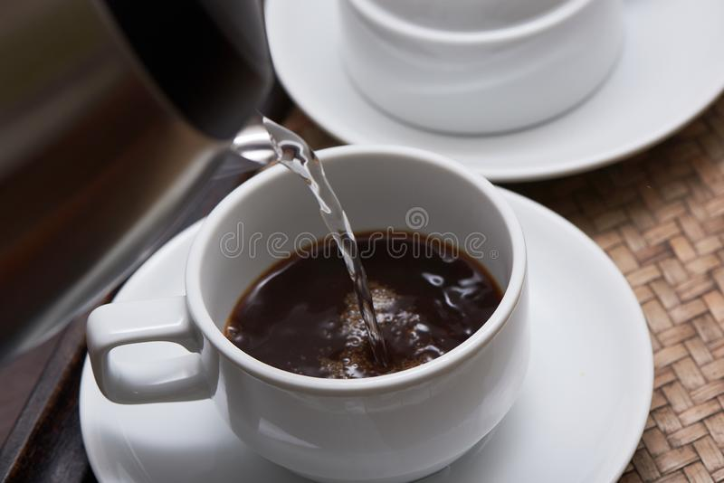 Лить горячая вода от чайника в кофейную чашку стоковые фотографии rf