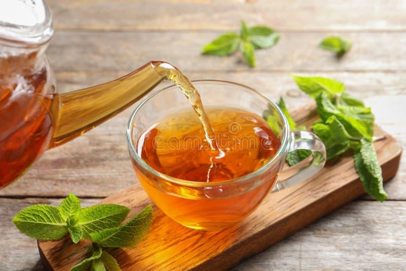 Лить горячий ароматичный чай мяты в чашку стоковые фото