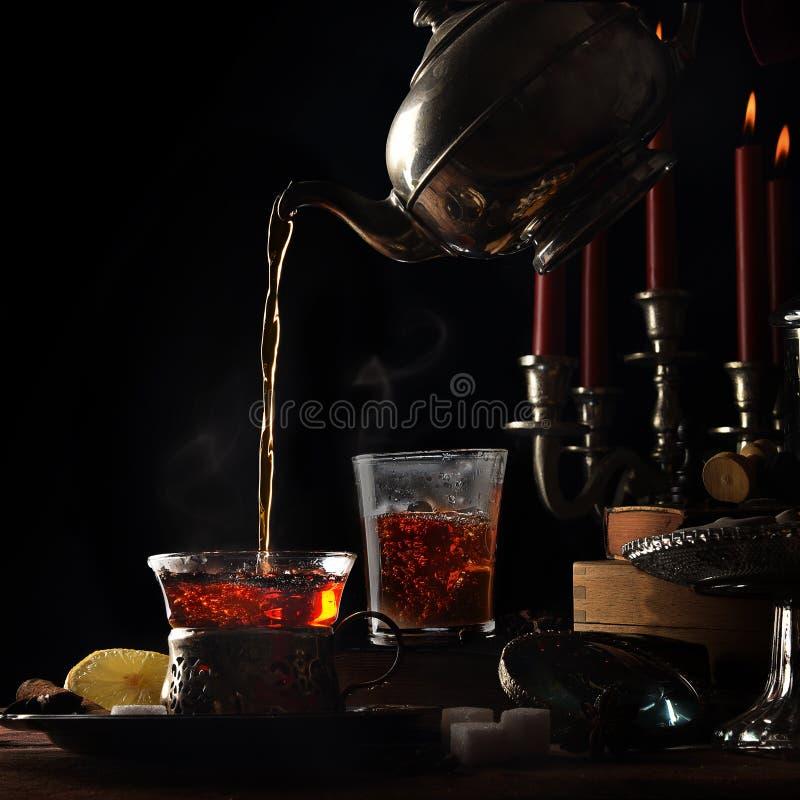 Лить горячий испаряясь чай от винтажного чайника в стеклянные чашки стоковые фото