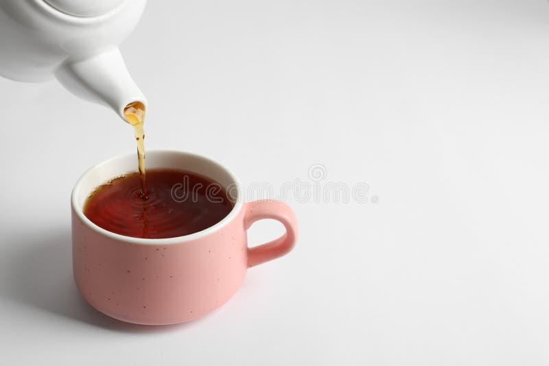 Лить горячий чай в керамическую чашку стоковое фото rf