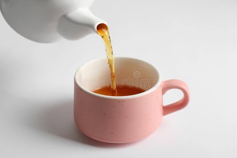 Лить горячий чай в керамическую чашку стоковые изображения