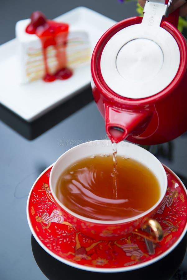Лить горячий чай в красной чашке стоковое фото rf