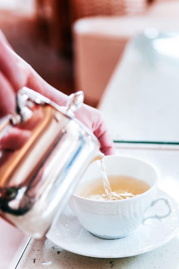 Лить горячий чай в чашку белого фарфора керамическую стоковые изображения rf