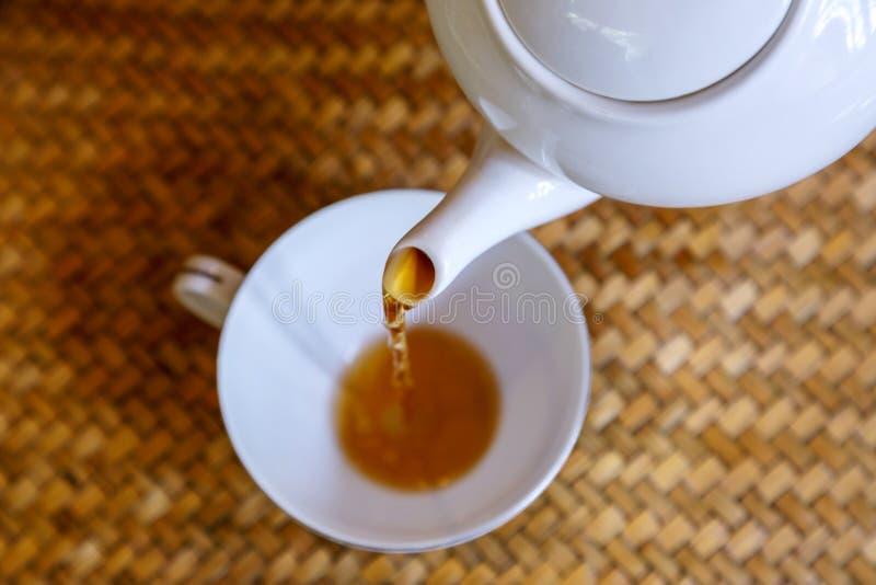 Лить горячий чай в чашку чая внутри тайской руки производит поднос стоковые фотографии rf