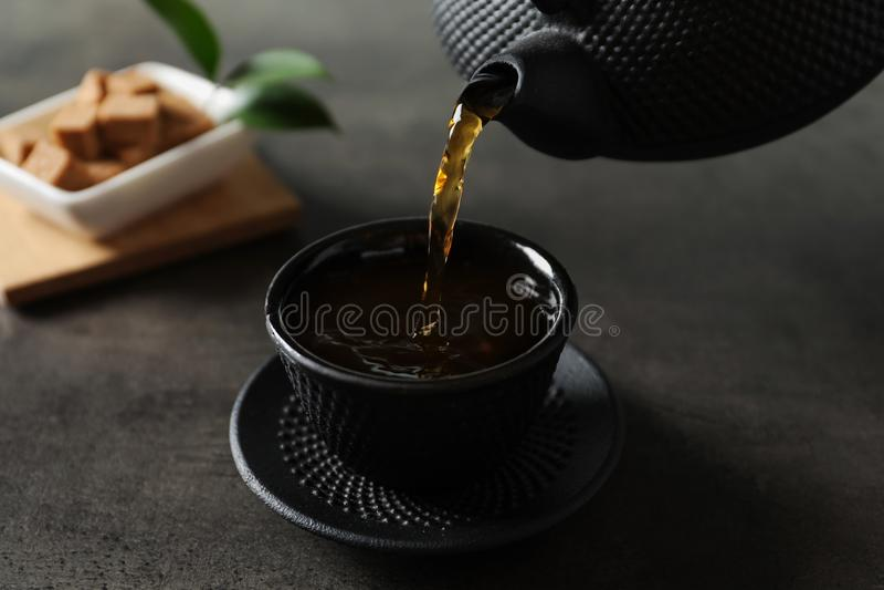 Лить горячий чай в черную чашку стоковые изображения rf