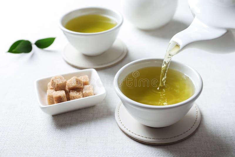 Лить зеленый чай в белую чашку фарфора стоковая фотография