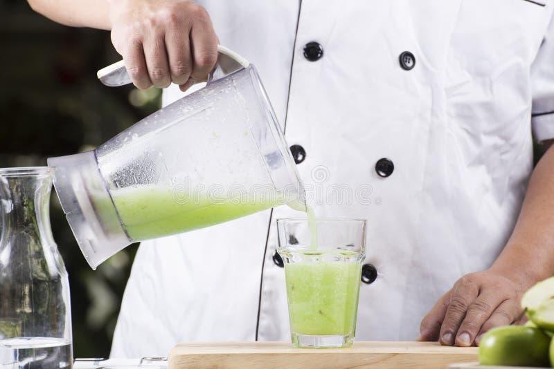 Лить зеленый smoothie Яблока к стеклу стоковые изображения