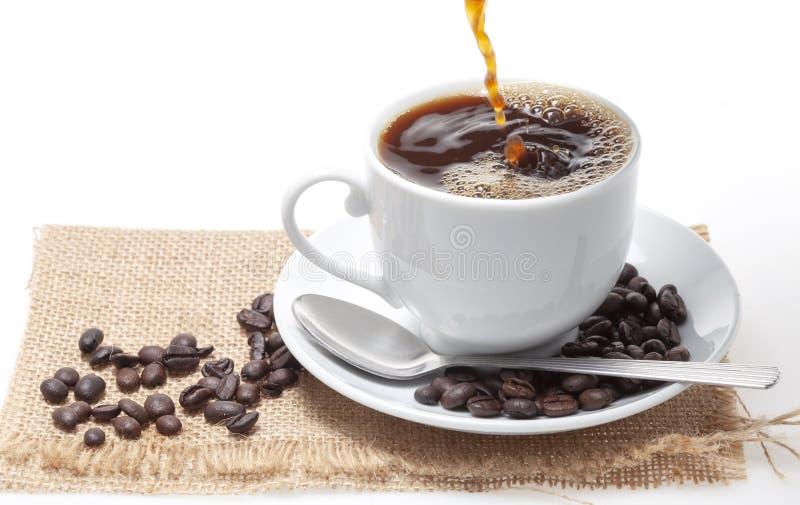 Лить кофе в белую кофейную чашку и фасоли на белой предпосылке стоковое фото rf