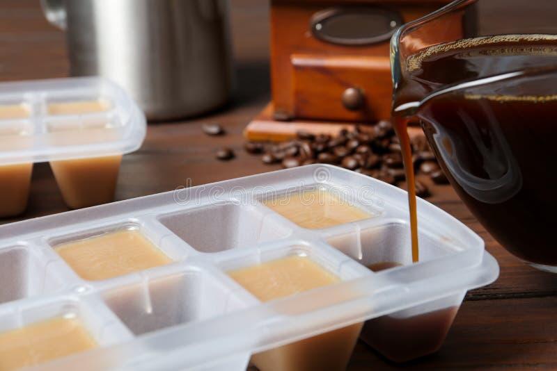 Лить кофе в подносе куба льда на таблице стоковое изображение rf