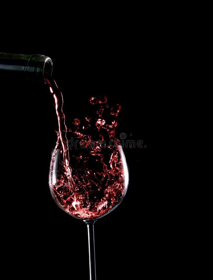 Лить красное вино, бутылка вина и рюмка стоковое фото rf