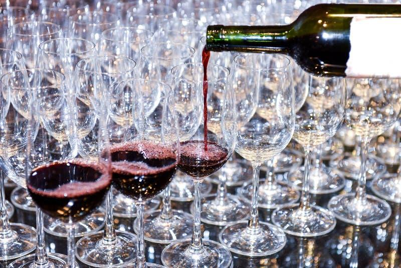 Лить красное вино в много стекла стоковые фотографии rf