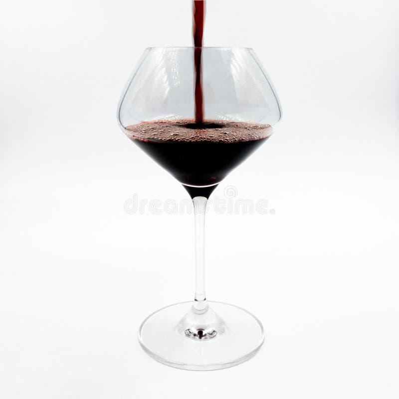 Лить красное вино в рюмке стоковые изображения