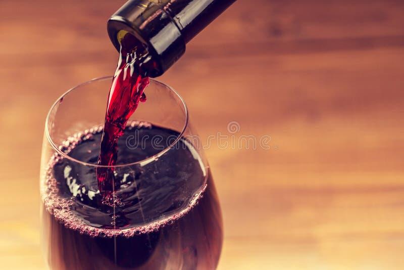 Лить красное вино в стекло против древесины стоковое изображение