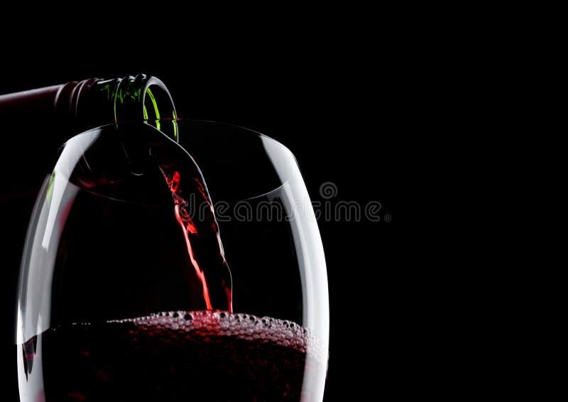 Лить красное вино от бутылки к стеклу на черноте с космосом для вашего текста стоковая фотография rf