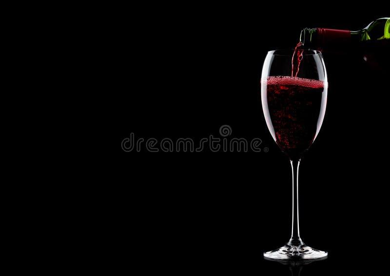 Лить красное вино от бутылки к стеклу на черноте с космосом для вашего текста стоковые изображения