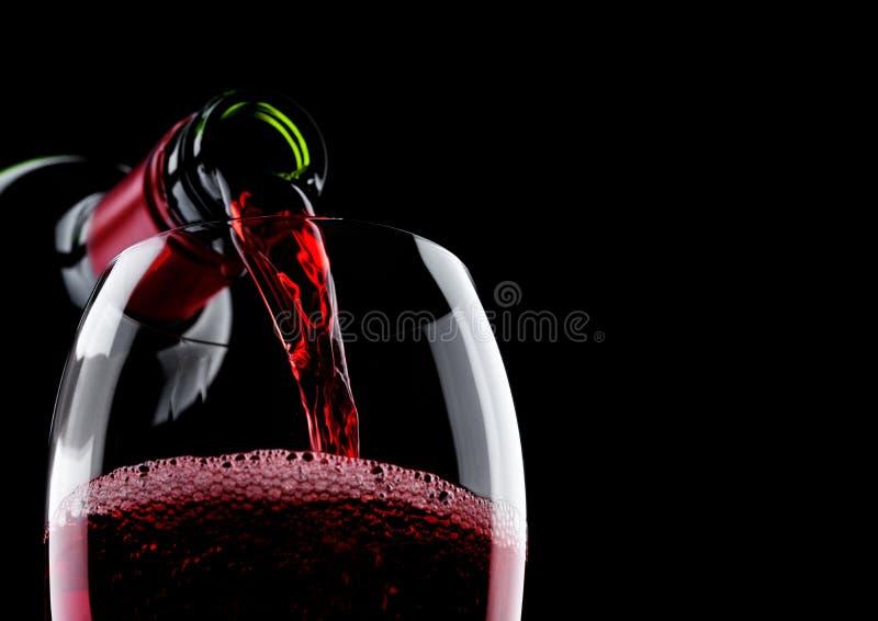 Лить красное вино от бутылки к стеклу на черноте с космосом для вашего текста стоковая фотография