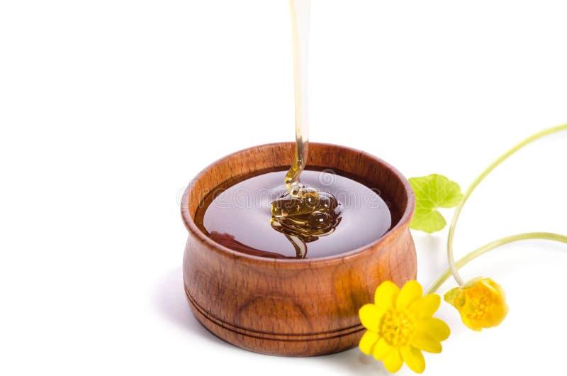 Лить мед в деревянном шаре с желтыми цветками стоковые фотографии rf